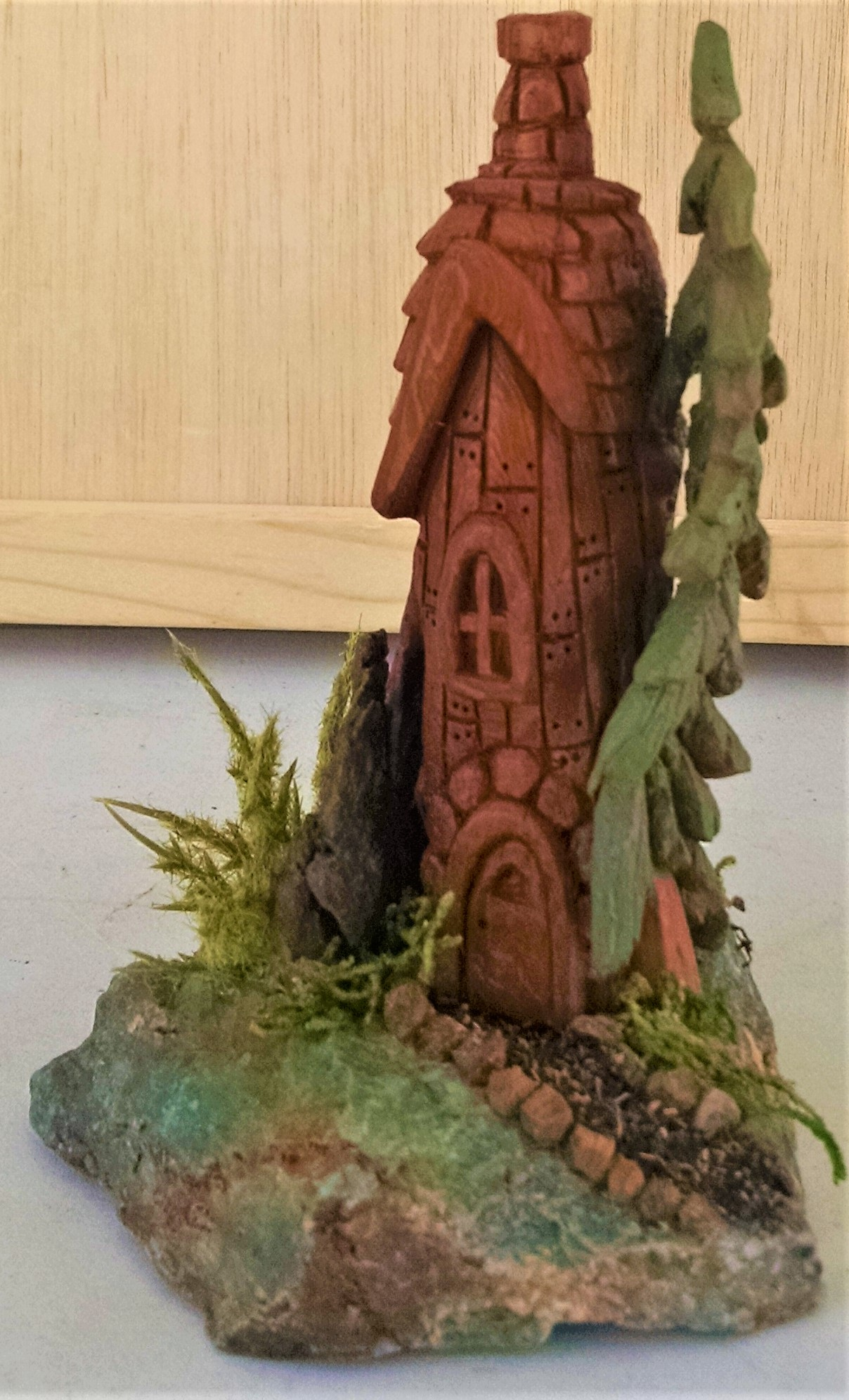 Fairy house with rock yard and pine tree side view